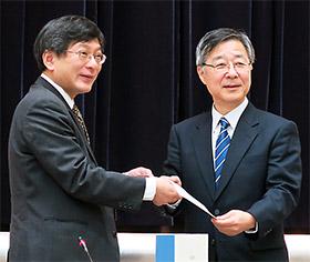 田辺国昭中医協会長(左)が意見書を厚労相代理の唐澤剛保険局長に手渡した