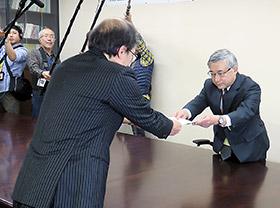 中垣医薬・生活衛生局長が処分通知を宮本理事長に手渡した