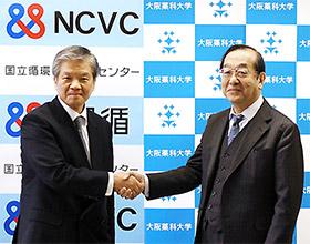 握手する国循の小川理事長、大阪薬大の政田学長