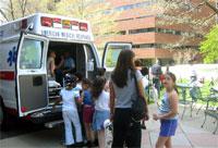 救急車を見学する子供たち。背景のテントや子供たちがはしゃいでいる様子が見えるでしょうか?