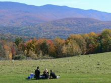 トラップファミリー・ロッジの敷地内でピクニックを楽しむ人々。澄み渡った秋晴れの高原で、奇麗な景色を眺めながらのランチは、会話も弾み楽しそうです。