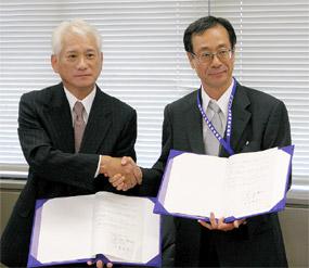調印式で握手する五十嵐筑波大病院長(右)と吉富三菱化学メディエンス社長