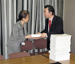 根本氏(右)が山本氏に署名を手渡す