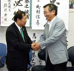 NHKテレビで当確がうたれ、喜び合う児玉孝選対本部長(左)と松本純議員