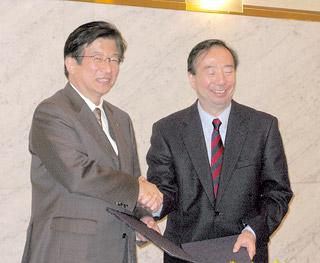 握手をする川勝知事(左)と清家塾長