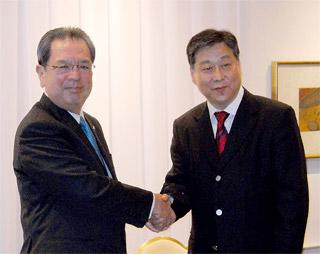 業務提携を締結して握手する三木田氏(左)と劉氏