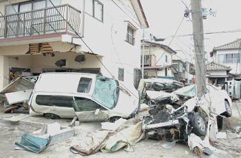 津波で流された車が電柱に突き刺さっている