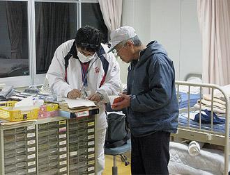 避難所で薬の説明をする長谷川氏