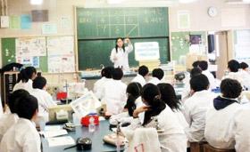 教員の説明に熱心に聞き入る白衣姿の児童たち