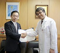 握手する内藤院長(右)、村岡薬学部長