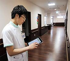 隣接する住宅型有料老人ホームで訪問薬剤管理指導業務を行う高橋さん。携帯端末を使って薬歴や相互作用をその場でチェックしている