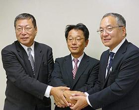 会見で握手する(左から)田尻、大野、秋野の各社長