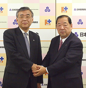 がっちりと握手する児玉氏(右)と山本氏