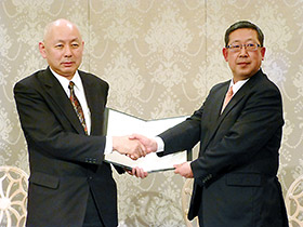 調印後、握手するAJD杉山社長(左)と全日食平野社長