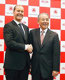 会見後握手するウェバー氏(左)と長谷川氏