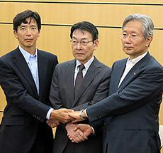 会見後に握手する3者の代表