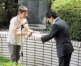 「誓いの碑」前で要望書を田村厚労相に渡す薬被連代表世話人の花井十伍氏(左)