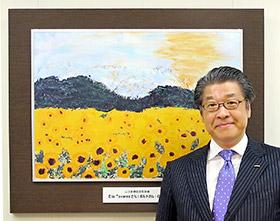 患者が描いた絵画を背景に立つ足利社長