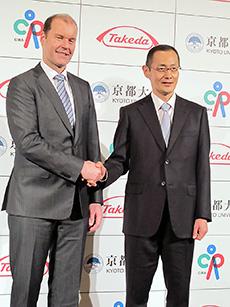 握手するウェバー社長(左)と山中氏
