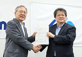 握手するPMDA近藤理事長(左)とAMED末松理事長