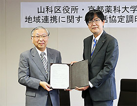 協定書を掲げる京都薬大学長の乾氏(左)、山科区長の堀池氏