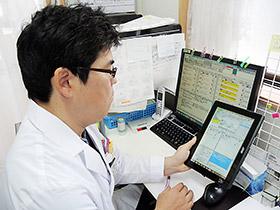 電子薬歴機能を備えたレセコン「ファーミー」(左奥)と、その機能をタブレットパソコンに搭載した「おでかけファーミー」(右手前)