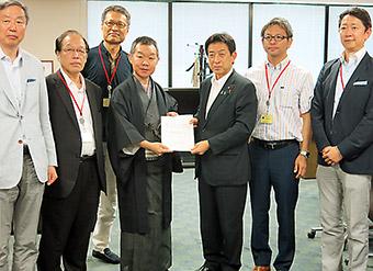 報告書を手渡す本荘座長(中央左)