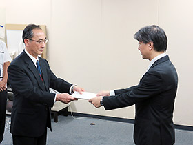 伊澤監視指導・麻薬対策課長(右)が処分通知を木下理事に手渡した