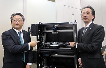 自動解析装置とヒロツバイオ代表取締役の広津崇亮氏(左)、日立製作所・基礎研究センタ主任研究員の久野範人氏