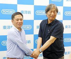 握手を交わす東洋紡の西山重雄執行役員(左)と富山大学の黒崎文也教授