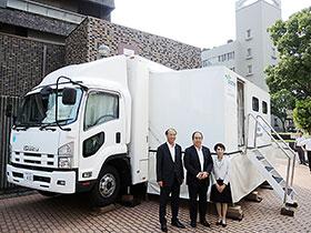 無償で貸し出されるデモ車と、提携した3者の代表者(中央=兵庫県薬・笠井秀一会長)