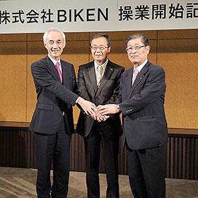 手を取り合うBIKEN財団・山西弘一理事長(右)、田辺三菱製薬・三津家正之社長(左)、BIKEN・宅康次社長