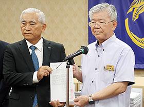 亀谷沖縄県薬会長(左)が大城琉球大学長に要望書と署名を手渡した