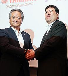 握手を交わす左からヤマハの藤田氏、イーベックの土井氏