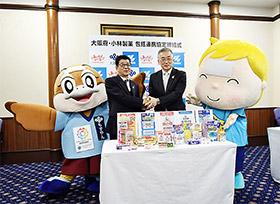 握手を交わす松井知事(左)と山根専務、大阪府のマスコットキャラクター「もすやん」と、小林製薬のキャラクタ-「熱さまくん」も登場