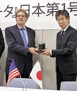 ゲラマン博士(左)から日本第1号機を受け取るキリン堂の寺西社長