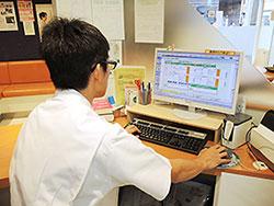 投薬窓口で端末に表示された内容を確認しながら、その患者に応じた副作用の説明を行う