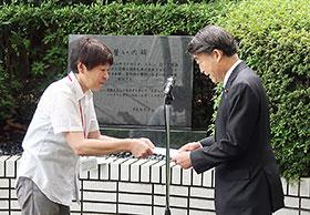 「誓いの碑」前で要望書を根本匠厚労相に渡す薬被連代表世話人の花井十伍氏(左)