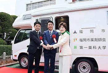 握手を交わす左から田中市薬会長、高島市長、都築学長