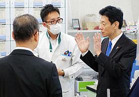 視察する西村康稔大臣(右)