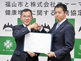 連携協定締結で握手を交わす枝広福山市長(左)とファーマシィの山中社長