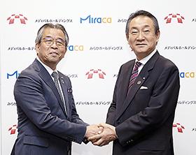 握手するみらかホールディングス・竹内成和社長(左)とメディパルホールディングス・渡辺秀一社長