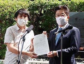 「誓いの碑」前で薬被連代表世話人の花井十伍氏(左)が要望書を加藤勝信厚労相に渡した