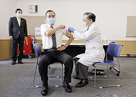 国内で初めて新型コロナウイルスワクチンを接種する新木病院長(中央)