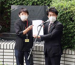 「誓いの碑」前で薬被連代表世話人の花井十伍氏(左)が要望書を田村厚労相に渡した